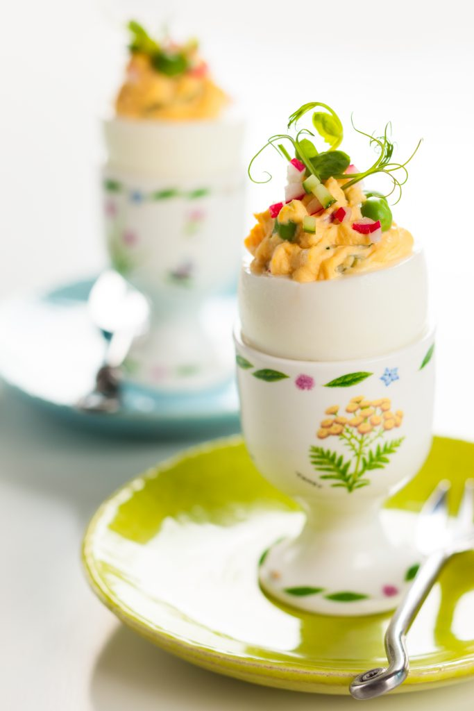 Deviled eggs with fresh cucumber, radish, and green pea shoots.